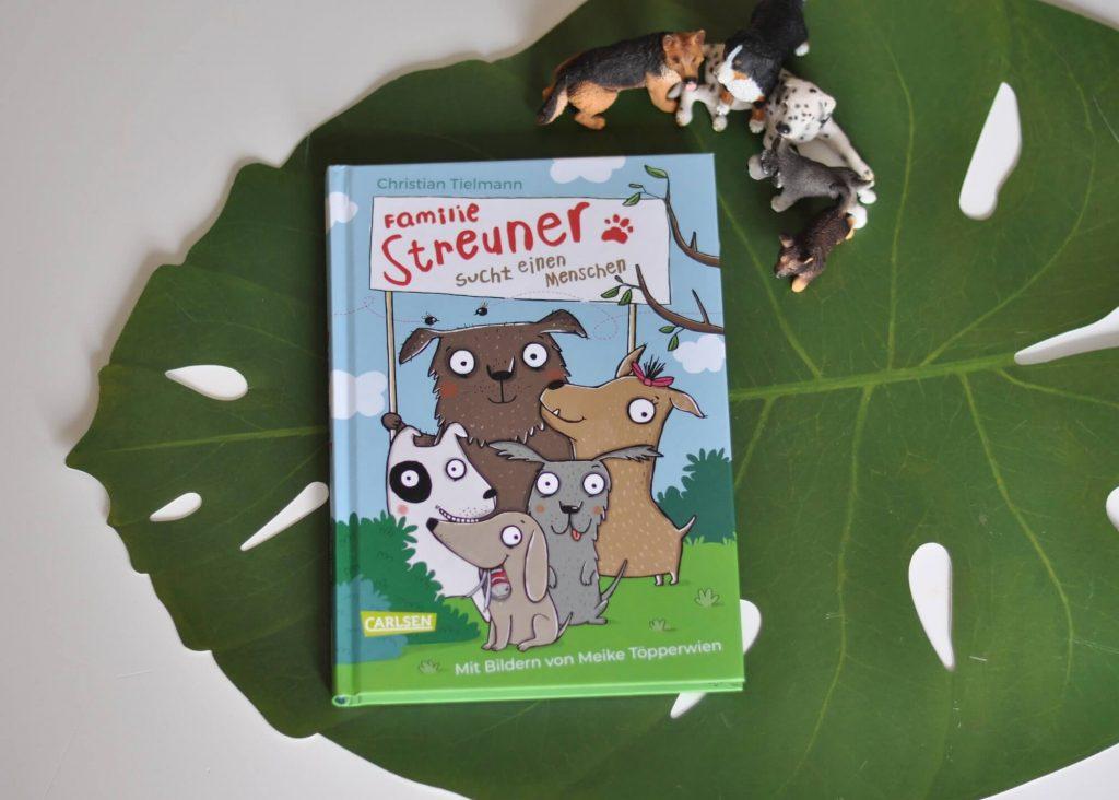 Die Hundefamilie Streuner lebt in einem gemütlichen Erdloch am Stadtrand – bis sich eines Tages die Wildschweine im Wald zusammenrotten und die Familie vertreiben wollen. Doch so einfach lassen sich die Streuners nicht unterkriegen. Schnell muss ein Wach- und Hütemensch her! Doch wo findet man den richtigen Zweibeiner? #hunde #lesen #kinderbuch #haustier #lustig