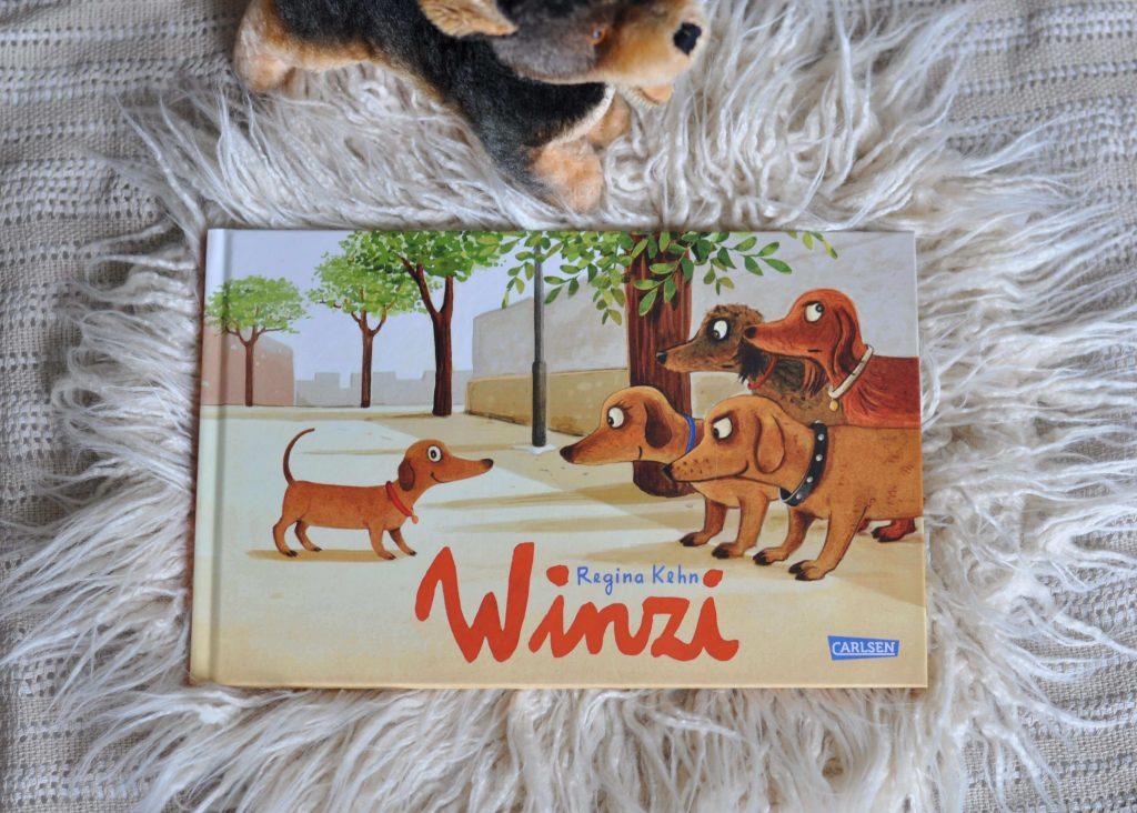 Winzi ist zwar der kleinste in seinem Wurf, aber er hat es faustdick hinter den Ohren. Von den Eltern lernt er zusammen mit seinen Dackelgeschwistern Poldi, Jule, Max und Gerda alles, was wichtig ist. So entdecken sie die Welt und hecken dabei gemeinsam jede Menge Unfug aus. Eines Tages zeigt sich jedoch, dass gerade der Kleinste der Mutigste von ihnen allen ist. #hund #dackel #bilderbuch #buch #vorlsen #klein