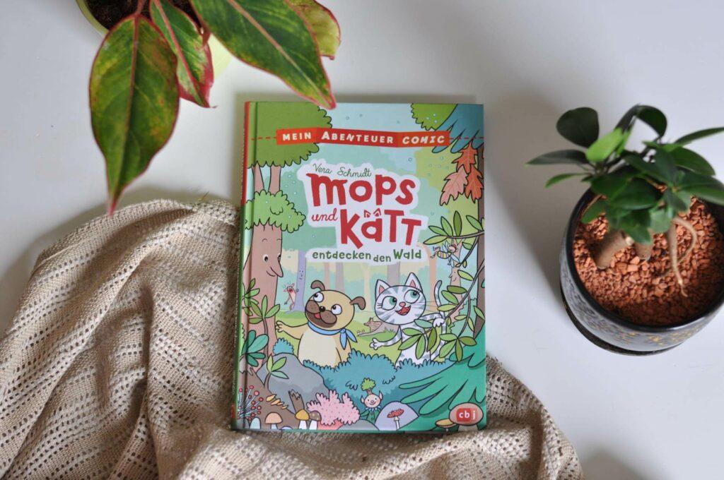 Mops und Kätt sind allerbeste Freunde. Doch während Kätt das Abenteuer sucht, hängt Mops lieber faul auf dem Sofa rum. Deshalb muss Kätt Mops auch ganz schon überreden, einen Spaziergang im Wald zu machen. Und der kommt maulend mit. Als die Freunde auf Rocky - einen rosa Rehbock treffen - wird das Waldspaziergang doch sehr spannend.  #kindercomic #sachbuch #lesen #leseanfänger #wald #entdecken #ferien #ausflug #wandern